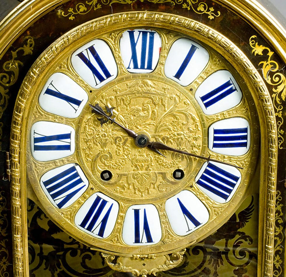 Ornate gold clock face with dark blue roman numerals